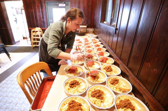"The Tandem's chef-owner, Caitlin Cullen, readies some of the hundreds of free community meals the restaurant has given out since Wednesday. ""We're going to cook these meals until we can't,"" she said, ""there's no food, there's no money, we're locked up."""