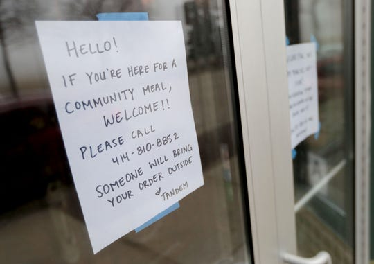 A sign on the door of the Tandem, a Southern-style restaurant at 1848 W. Fond du Lac Ave., to call the restaurant to have their community meal brought to them.