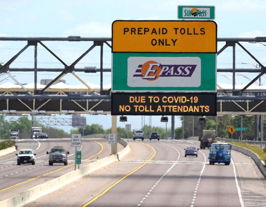A traffic alert sign tells drivers eastbound on S.R. 414 in Apopka, Fla., that toll plazas are unstaffed due to the coronavirus response, Friday, March 20, 2020. All toll roads managed by the Florida Department of Transportation, including the Florida Turnpike, will no longer staff plazas to take cash due to the coronavirus crisis. Tolls will be billed electronically by Toll-By-Plate until further notice.