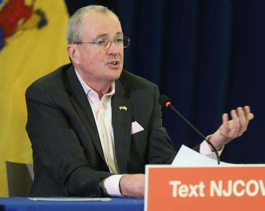 """The daily briefing by Governor Phil Murphy announces his executive order closing all non-essential businesses while discussing the corona virus at Rutgers University in Newark on March 21, 2020 so as to give more room for """"social distancing"""" to members of the media and his experts being interviewed."""