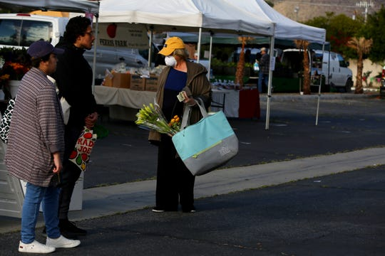 Kathy Weremiuk of Palm Springs, center, wears a mask as she shops at the Certified Farmers' Market in Palm Springs, Calif., on Saturday morning, March 21, 2020. The market has a single point of entry and exit to regulate the amount of people on the grounds in order to practice social distancing and mitigate the spread of coronavirus.