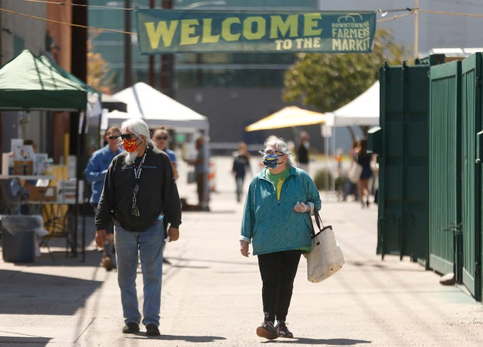 Susanna Yazzie (R) and her husband leave the downtown Farmer's Market in Phoenix, Ariz. on March 21, 2020.