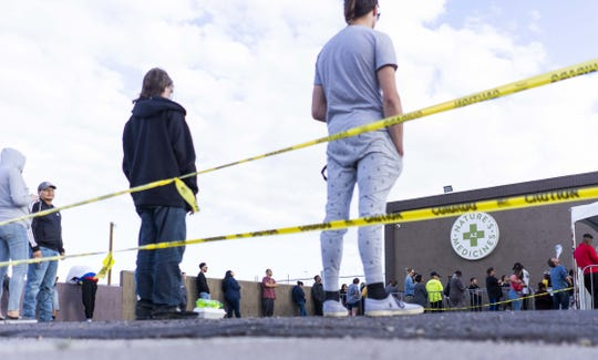 People wait in line outside Nature's Medicines in Phoenix while waiting in line to get into the store on March 20, 2020.