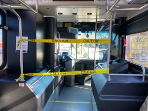 """Yellow caution tape separates the driver and passenger areas inside a Valley Metro bus in Phoenix and a sign reads, """"Thank you for keeping a safe distance from each other and the operator"""" on March 21, 2020."""