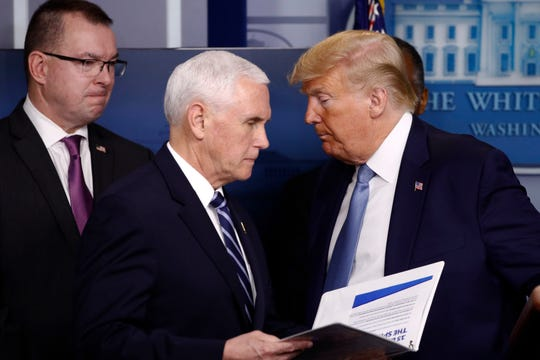 Vice President Mike Pence walks to the podium as President Donald Trump looks on during a coronavirus task force briefing at the White House on Saturday, March 21, 2020, in Washington.