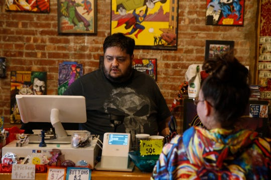 Albert Mas, owner of The Underground Beacon comic book store helps a customer on March 20, 2020.