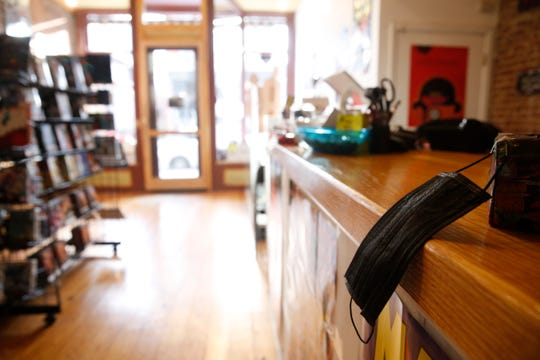A black surgical mask hangs from the register at the Underground Beacon comic book store on March 20.