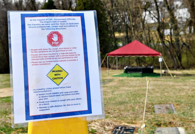 A sign is posted regarding COVID-19 restrictions and safety protocol prior to a committal service at Mount Rose Cemetery in Spring Garden Township, Saturday, March 21, 2020. Dawn J. Sagert photo