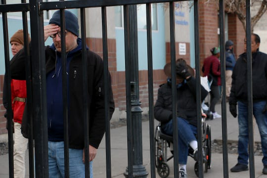 Carl Streeter, front left, and others wait to be let into the homeless shelter on Record Street in Reno on March 20, 2020.