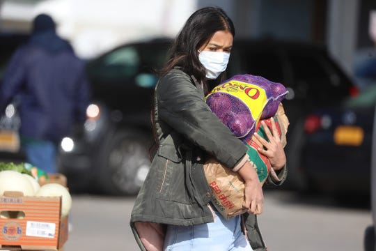 Dipa Bista, who was shopping at the Rochester Public Market with her sister, Purna, leaves with some items Saturday, March 21, 2020.  Fewer people shopped at the Rochester Public Market which normally draws a large crowd on Saturdays.