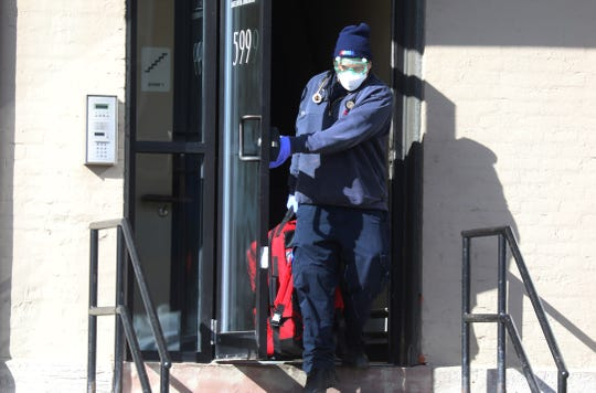 Police and emergency responders now wear masks and eye protection to protect themselves form COVID-19 when they respond to calls like this EMT that left an apartment building on Lake Ave., in Rochester,  Saturday, March 21, 2020.