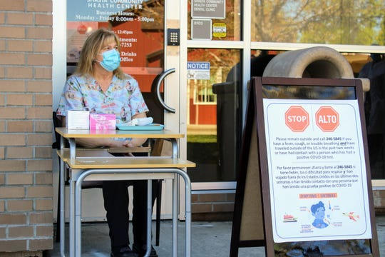 Cheryl Russo of the Shasta Community Health Center sits outside to screen people for coronavirus symptoms in downtown Redding on Friday, March 20, 2020.
