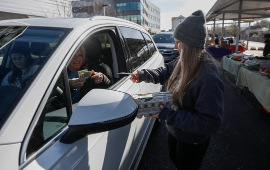 Payton Dennis, of Morning Sun Farms, hands Beverly Quinn two dozen eggs at the Farmers Market of the Ozarks on Saturday, March 21, 2020. The market was converted into a drive-thru as a precaution taken to stop the spread of the coronavirus.