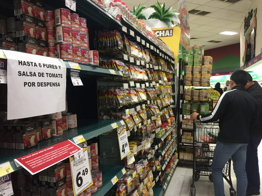 Shoppers in Juárez on Friday, March 20, 2020, only buy the essentials as signs on shelves announce a limit of items per household.