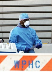 A medical worker walks out of a Coronavirus screening tent set up outside the emergency room at White Plains Hospital  March 21, 2020.