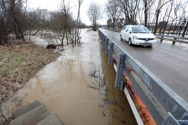 Wakatomika Creek flows under the bridge and over its banks on Shannon Road near Frazeysburg on Friday.