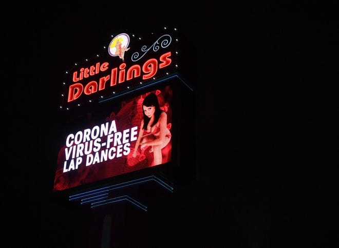 """A sign at Little Darlings Las Vegas strip club advertises """"coronavirus-free lap dances"""" despite a 30-day shutdown of nonessential businesses recommended by Nevada Gov. Steve Sisolak this week to help fight the spread of the coronavirus on March 19, 2020, in Las Vegas, Nevada. The strip club will reportedly start offering drive-through strip shows with dancers adhering to the six-foot separation guideline recommended by the Centers for Disease Control and Prevention for patrons who don't want to enter the building. The club is also planning on holding a nude hand sanitizer wrestling show. The World Health Organization declared the coronavirus (COVID-19) a global pandemic March 11."""