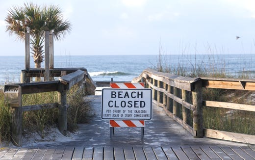 Signs block the paths to the beach at the Okaloosa Island, Florida, Boardwalk, Saturday, March 21, 2020, as beach closure orders are in effect for Walton and Okaloosa Counties in the Northwest Florida panhandle.