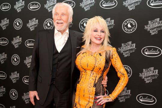 """Kenny Rogers, left, and Dolly Parton walk the red carpet of the """"All In For The Gambler: Kenny Rogers' Farewell Concert Celebration"""" at Bridgestone Arena on Wednesday, Oct. 25, 2017, in Nashville. Rogers and Parton frequently worked together and released several notable duets, including 1983's """"Islands in the Stream."""""""