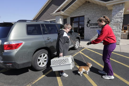 CountrySide Veterinary Services changed the way it did business this week in response to the coronavirus. Here, Sandy Pieper, left, of Menasha hands off her cat Freddy and dog Gabby to Maddie Opperman, a veterinary technician. Clients were asked to drop off their animals outside to limit the amount of people entering the building.