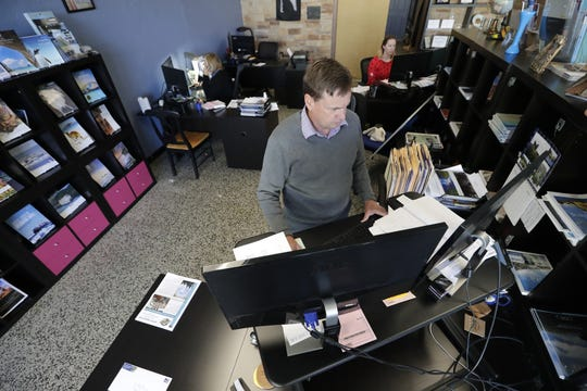 Geoff Hendren, co-owner of BonVoyage Boutique Travel in Neenah, works on re-scheduling a customer's vacation trip. In back, co-owner Cindy Hendren is on the left and their daughter, Kara Rothkegel, is on the right. Rothkegel will be laid off this next week as the company struggles to stay afloat.