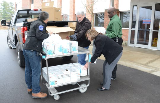 Officer Marc Pierce, left, from Kellogg Community College, Jane Janssen from Bronson Healthcare, her husband Kurt, and Austin Simons, KCC Police Chief, load masks Thursday donated by the college to the hospital system.