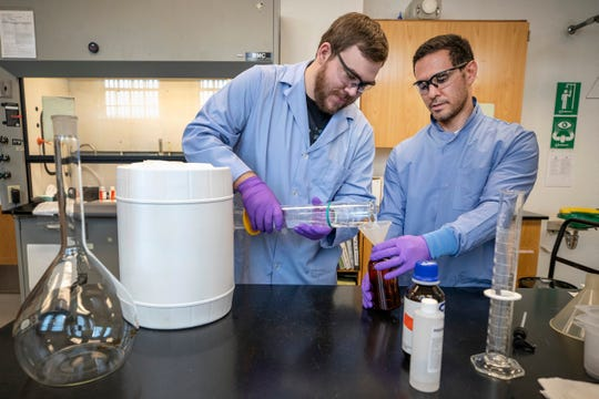 Chemists Anthony Painter, left, and Deniz Ferrin, right, make hand sanitizer Friday at the Puget Sound Naval Shipyard.