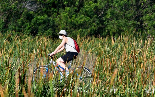 A bicyclist rides along a trail at the Ritch Grissom Memorial Wetlands in Viera before the closing went into effect.