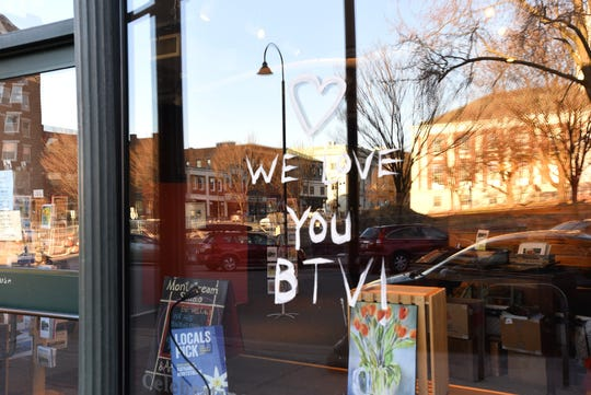 The storefront glass of Katharine Monstream's Monstream Studio on St. Paul Street in Burlington sends a message to city residents on Sunday, March 22, 2020. Many businesses including bars and restaurants are closed during the outbreak of COVID -19.