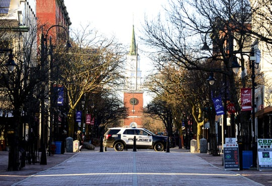 A police car on College Street crosses the Church Street Marketplace in Burlington on Sunday, March 22, 2020. Only a few people were out in downtown Burlington Sunday afternoon as many businesses including bars and restaurants are closed and many people are staying home during the outbreak of COVID -19.
