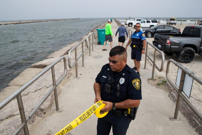 A Corpus Christi police officer tapes off the jetties on Sunday, March 22, 2020 to prevent public access. Police also closed roads into Corpus Christi beaches and encouraged potential beach goers to practice social distancing to stop the spread of COVID-19.