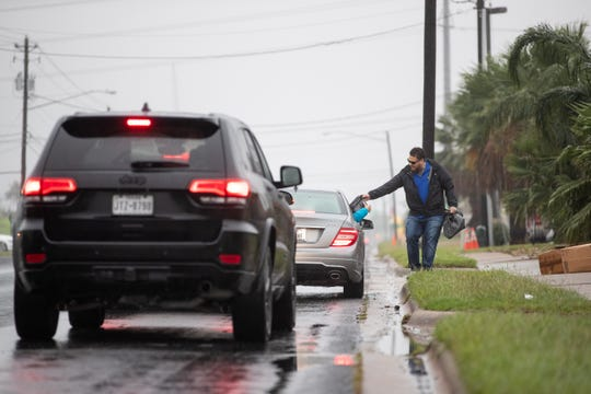 Daniel Gutierrez hands out 400 rolls of toilet paper for free to people infant of The Den Nutrition on Airline Road on Saturday, March 21, 2020.