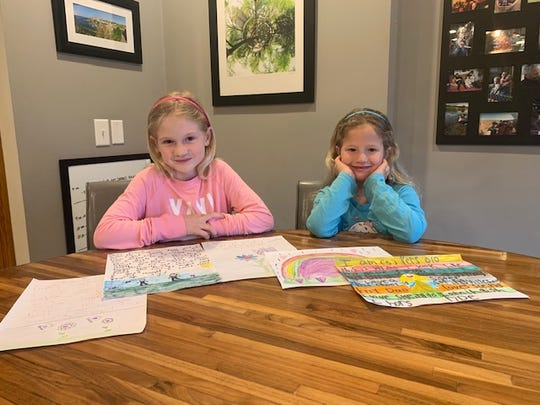 Izzy, left, and Pippa  Hines of Mount Laurel draw pictures and write notes to isolated senior citizens in their home.