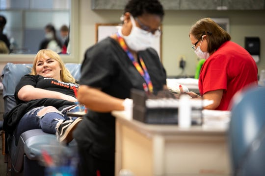 Caroline Braun, of Crestview Hills, donates blood as Hoxworth employees (foreground) Sheila Morning and Sylvia Lokesak, prep other materials on Sunday, March 22 at the Hoxworth Blood Center in Fort Mitchell.