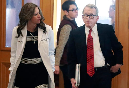 Ohio Department of Health director Dr. Amy Acton, left, and Gov. Mike DeWine walk into a coronavirus news conference Sunday, March 22, 2020 at the Ohio Statehouse in Columbus, Ohio. (Doral Chenoweth/The Columbus Dispatch via AP)