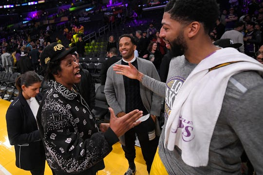 Rapper Jay-Z, left, talks with Los Angeles Lakers forward Anthony Davis after a game between the Lakers and Bucks on Friday, March 6, at the Staples Center.