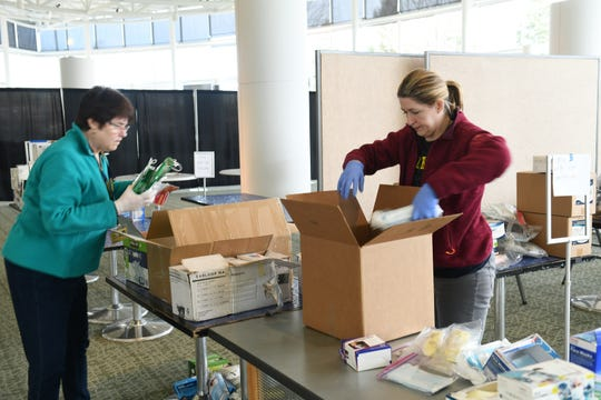 From left, UM Medical School supply chain value analyst and RN Pat Kielezewski and project manager Corrie Pennington-Block box up some of the donated supplies that are opened or are hard to categorize.  Donations of medical protective gear are received at the University of Michigan North Campus Research Complex in Ann Arbor, March 22, 2020.