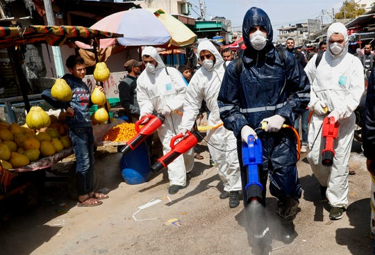 Workers wearing protective gear spray disinfectant as a precaution against the coronavirus, at the main market in Gaza City, Thursday, March 19, 2020.