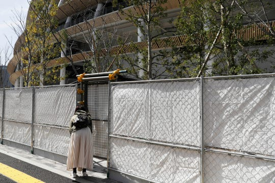 A woman peeks through a fence Saturday surrounding the Olympic Stadium in Tokyo. The Olympic flame from Greece arrived in Japan Friday, even as the opening of the the Tokyo Games in four months is in doubt with more voices suggesting the games should to be postponed or canceled because of the worldwide virus pandemic.