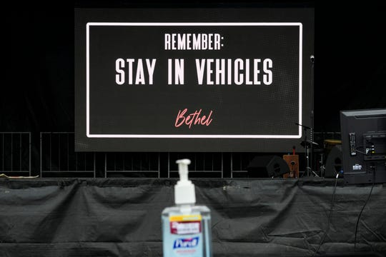 A video screen reminds congregants to stay in their vehicles during a drive-in church service held outside of Bethel Church in Evansville, Ind., Sunday, March 22, 2020. The church hosted the drive-in services in light of the COVID-19 pandemic, allowing congregants to safely watch from their parked cars and listen to the service via radio.