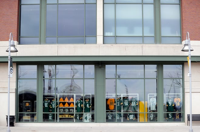 Football jerseys and cheeseheads are seen through the windows of the Packers Pro Shop. The store will be the first to offer Green Bay Packers NFC championship gear if the Packers defeat the Tampa Bay Buccaneers on Sunday.
