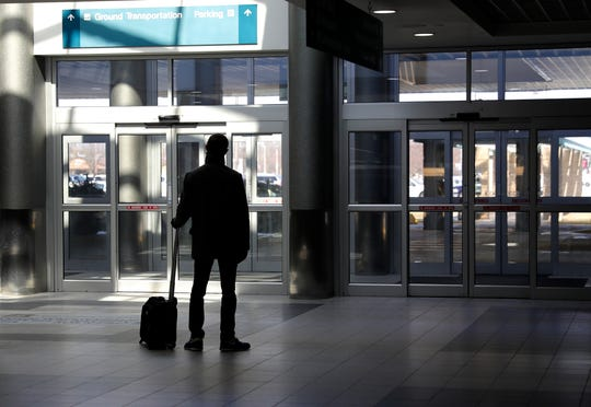 A traveler waits by the front doors of Green Bay Austin Straubel International Airport on March 20, 2020, in Ashwaubenon, Wis.