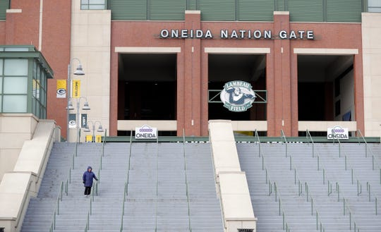 A lone individual walks the steps outside Lambeau Field on March 20 in Green Bay . Lambeau Field Atrium businesses, including the Packers Pro Shop, Packers Hall of Fame and 1919 Kitchen & Tap, are temporarily closed due to the coronavirus pandemic.