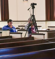 Andrew Cronic sits by the video camera for a live online broadcast of Capstone Church praise band during worship in the nearly empty church sanctuary in Anderson, S.C. Sunday, March 22, 2020. The church usually has 200 in attendance but with many practicing social distancing, the online broadcast helps deliver the service.