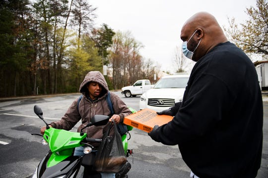 Pastor John Gray hands Bruce Gaffney groceries and a pizza at Relentless Church Sunday, March 22, 2020.