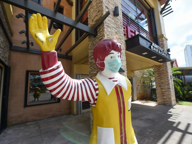 A Ronald McDonald statue is decorated with a respirator outside the Tumon McDonald's restaurant during the COVID-19 pandemic on Guam, March 22, 2020.