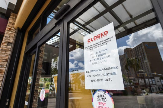 A sign of closure due to the COVID-19 pandemic is posted on a JP Superstore entrance in Tumon, March 22, 2020.