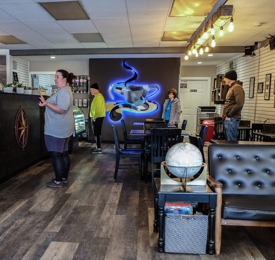 """Customers at Global Coffee in St. Johns appear to be practicing """"social distancing"""" as they wait for their takeout cups of coffee Saturday, March 21, 2020."""