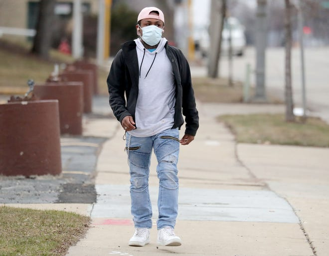 Tru Johnson, of Milwaukee, wears a face mask as he walks down West Hampton Avenue just east of West 84th Street in Milwaukee on Sunday, March 22, 2020. Johnson was wearing the mask to help him from getting infected by the coronavirus.
