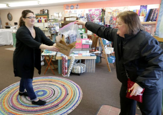 Stephanie Walter, right, of Menomonee Falls drops off a bag of face masks she made from a safe social distance at Log Cabin Sewing Co. in Butler on Sunday.  Log Cabin Sewing Co. owner ‎Donica Lintner‎, left, created the Facebook group The Masked Sewists for SE Wisconsin to make face masks and also to collect masks made by volunteers from the community.